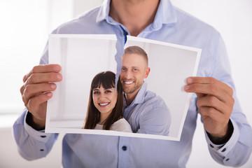 Man Tearing Photo Of Smiling Couple