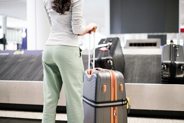 woman Waiting For Luggage From Conveyor Belt At Airport