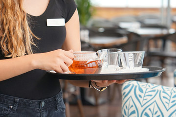 The waitress is carrying tea. Hospitable girl waitress holding tray with cup of tea and tea glass teapot for the client at the restaurant. The concept of maintenance and service. Close-up.
