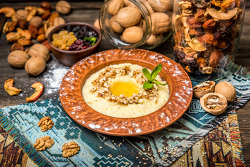 healthy breakfast bowl. oatmeal with nuts, and honey on wooden background