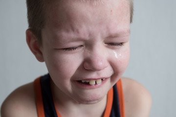 Boy cries with tears. Upset child. Violence in family over children. Concept of bullying, depressive stress or frustration. Close up view. Pure authentic emotion