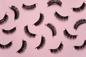 Black false lashes strips on pink background