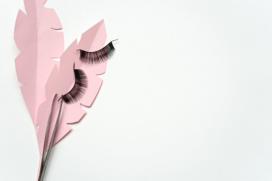 Black false lashes strips with tweezers on pink paper leaves and white background