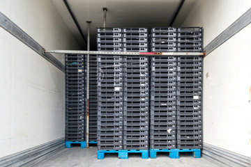 refrigerated semitrailer filled with transport crates on pallets