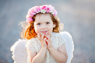 Beautiful little Angel girl with floral wreath standing with arms close to her chest as in prayer