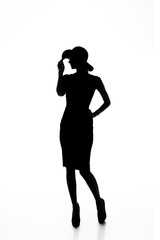 Silhouette of a slender young woman in dress and hat on white isolated background with place for text