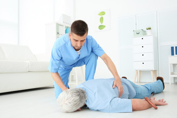 Young doctor giving first aid to senior man with heart attack in clinic