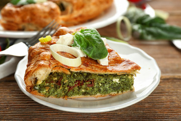 Piece of tasty pie with spinach on plate