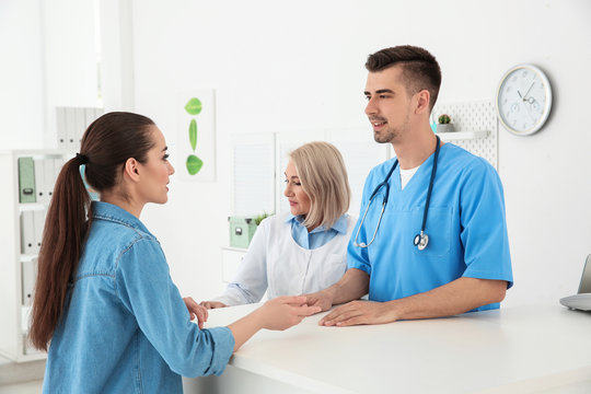 Young male doctor and senior female receptionist working with client in hospital