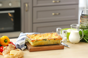 Baking tray with tasty spinach lasagna on kitchen table