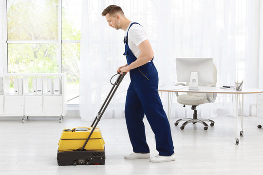 Male worker with floor cleaning machine indoors