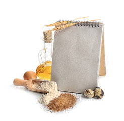 Composition with ingredients for homemade bread and notebook on white background