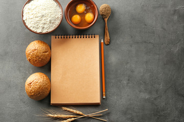 Notebook and products for making bread on grey background