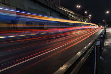 Time-lapse Photograph of Light Trails caused by cars driving along a road in the city.