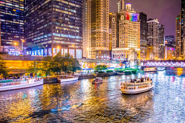 Beautiful downtown Chicago at night with lit buildings, river and bridge.