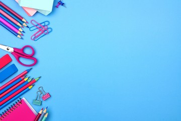School supplies side border against a pastel blue paper background. Pink and blue color theme.
