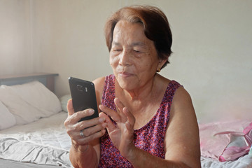 Elderly asian woman is pressing mobile phone with smiling
