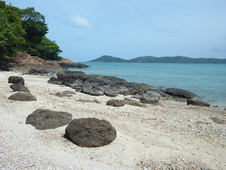 Deserted beach with large boulders and view of a turquoise ocean and distant mountains. Landscape of Koh Samed Island, Thailand.
