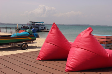 Comfy seating in the form of pink beanbags on a terrace facing the beach and boats docked at a pier on a tropical island in Thailand.
