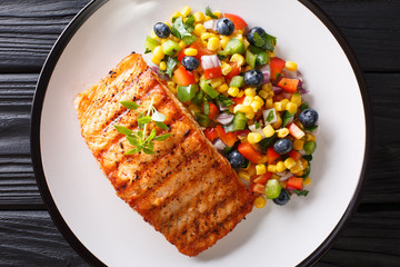 Grilled steak salmon with pepper, corn, blueberry and onion salad closeup on plate. horizontal top view