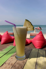 Glass of yellow pineapple fruit smoothie drink with a background of comfy pink beanbag cushions on a tropical beach