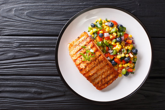 Freshly cooked grilled salmon filet with pepper, corn, blueberry and onion salad close-up. Horizontal top view