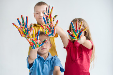 Three smiling kids with colourfull hands on white background closeup