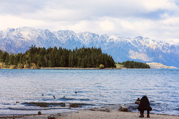 A Photographer Crouching Down To Take A Picture Of A Bird On The Banks Of Lake Wakatipu In New Zealand