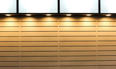 Wall with patterned wood background. The light that shines down illuminates the surface from above.