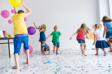 Group of  7 seven children play with air balloons, confetti in light room on birthday party