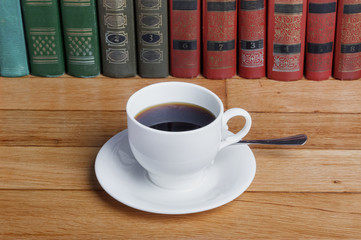 Hot cup of fresh coffee on the wooden table  with books