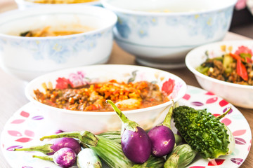 The poor eat a cup of spicy chili paste with vegetables and wild curry on a wooden table.