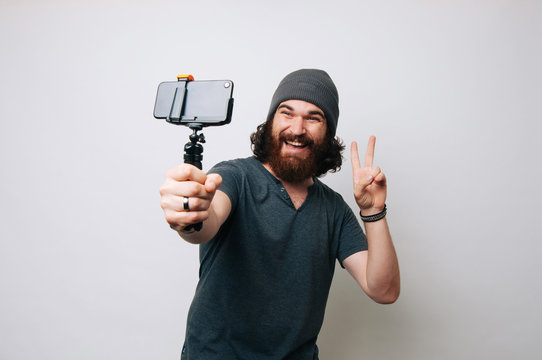 Happy amazed young bearded hipster man taking a selfie over white background