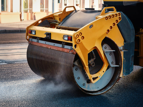 Modern heavy asphalt roller that stack and press hot asphalt. Yellow road repair machine. Repairing in modern city with vibration roller compactor