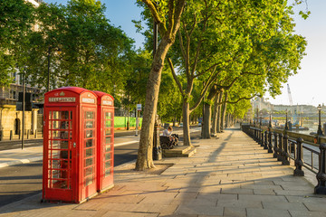 Photo sur Plexiglas Londres A traditional red phone booth in London at sunny morning