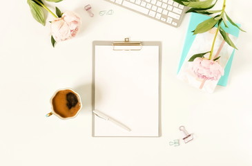 Flat lay women's office desk.Mockup with clipboard, keyboard , office accessories, notebooks, pen, cup of coffee,  pink peonies on white background.  top view. copy space
