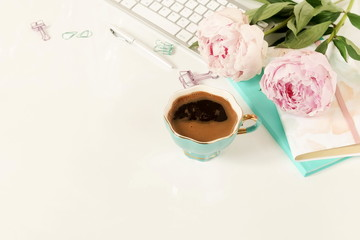 Flat lay women's office desk. Female workspace with laptop,  flowers peonies,  accessories, notebook, glasses, cup of coffee on white background. Top view feminine background.Copy space