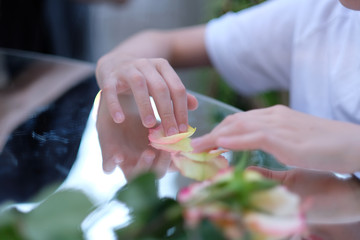 The hands of a child sitting at a table with a mirror surface and playing with rose petals.