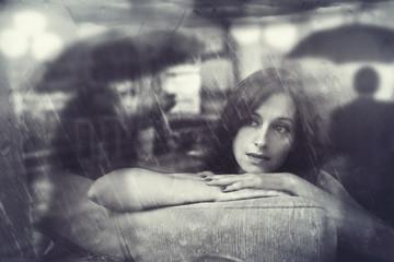 pensive woman looks on a rainy street