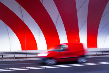 Fast driving red car in tunnel with red stripes