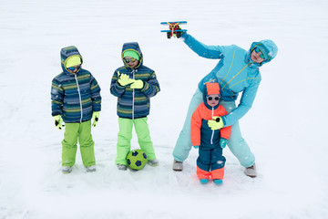 A happy mother with kids in sunglasses and a bright blue ski suit. Mother and children are happy together. A sports family on a snow-covered river with snow. Boys are very happy to play outdoors