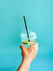 Glass of lemonade Woman is holding plastic glass with lemonade on blue background Photo mockup with copy space