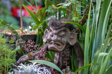 Statue primitive totem indonésien en bois représentant le dieu de la fertilité dans le jardin.