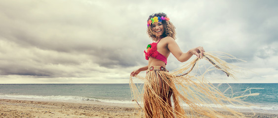 Happy and cheerful hawaiian woman portrait dancing on the beach, letterbox