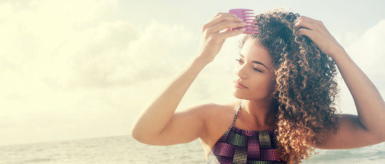 Woman portrait combing her gorgeous curly hair on the beach, letterbox