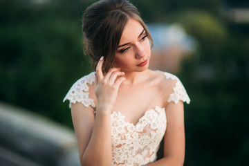 Teenage girl in wedding dress on city. Background town sunset
