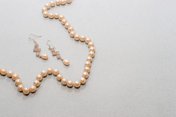 Beads and pearl earrings on a blue background, top view