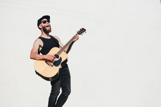 Guitar player singing outside. Hipster guitar player with beard and black clothes