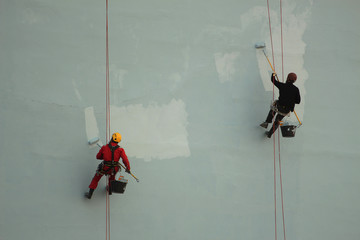 Industrial climbers paint the wall of the building