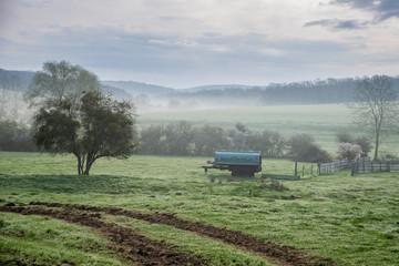 Trace d'un tracteur vers un pâturage avec son abreuvoir sur un paysage de brume à la campagne, avec au fond une forêt, près de Metz en Moselle